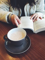 Girl reading a book in a cafe. Cup of coffee and book