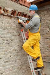 Worker demolish wall with electric plugger, chisel, hammer
