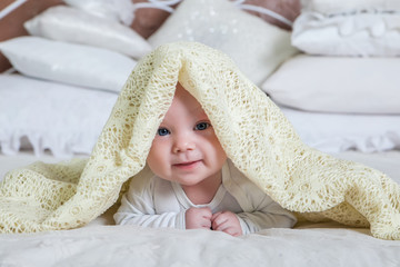 baby boy is hiding under the white blanket