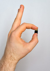 Male hand holding Micro SD card.