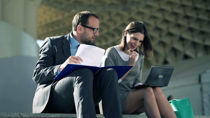 Businesspeople working with laptop, documents sitting on stairs