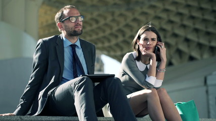 Businesspeople with laptop and cellphone sitting on stairs