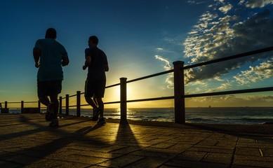 men running next to the sea at sunrise