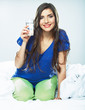 Woman in bed holding water glass.