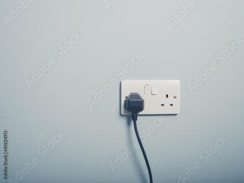 Leinwandbild Motiv UK wall socket and cord on blue wall