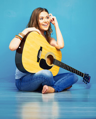 teenager girl with long hair sitting on a floor with guitar