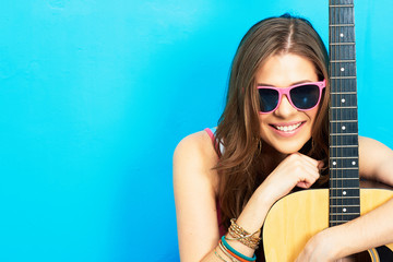 girl musician sitting on a floor with guitar