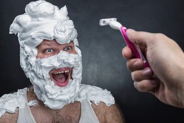 Surprised man with shaving foam on his face