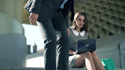 Businesspeople talking and working with laptop sitting on stairs