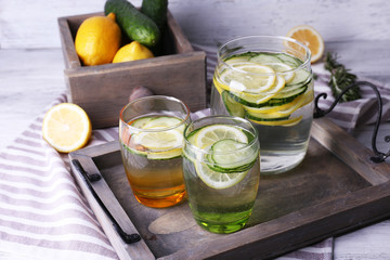Fresh water with lemon and cucumber in glassware in wooden