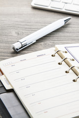 White ballpoint pen and leather weekly calendar