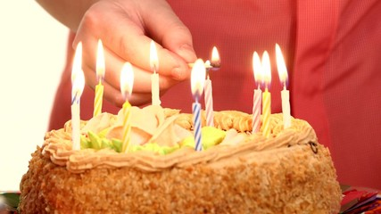 Hands of a little boy in turn lights the candles on the cake