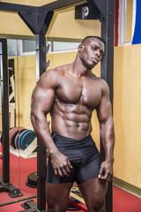 Handsome black male bodybuilder resting after workout in gym