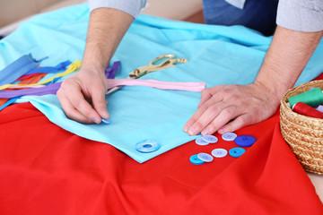 Male dressmaker tailor fabric on table