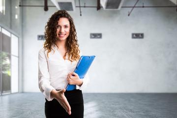 junge Geschäftsfrau mit Handschlag-Geste vor leerem Raum