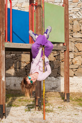 Girl playing on the court - hanging upside down.