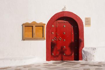 Red wooden door of the Greek monastery on the island of Mykonos.