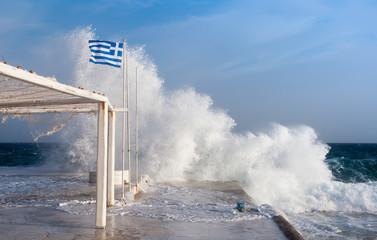 Waves crashing on the pier of the Mykonos island, Greece