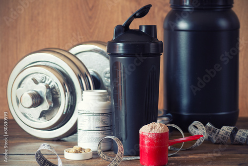 Whey protein powder in scoop with vitamins and plastic shaker - 80630593