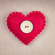 Red heart with a retro wooden button on fabric background