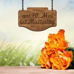 Rosen vor Wiese und Schild mit Muttertagshinweis