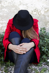the girl sitting on grass who wearing black fedora hat