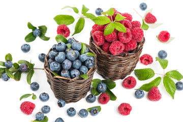 Blueberry and raspberry with leaves in a baskets