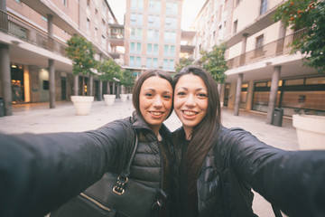 Female Twins Taking a Selfie in the City.