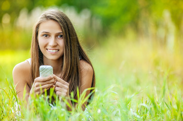 young woman grass lying with phone