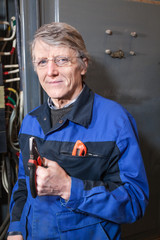 Mature electrician with pliers in his hands stands near box