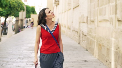 Attractive, young woman looking at ancient walls in Seville