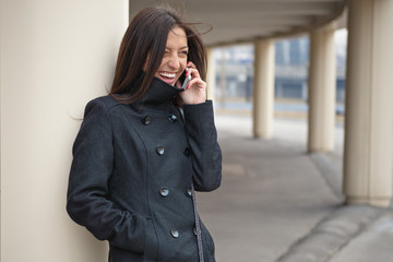Молода жизнерадостная девушка разговаривает по телефону.