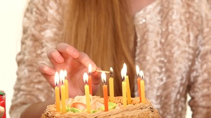 Hands of  little boy in turn lights candles on the cake. slow