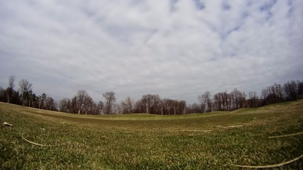 Static timelapse of clouds moving in a field