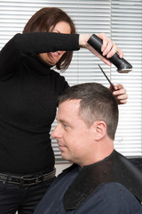 Hairdresser cuts hair with a electric razor