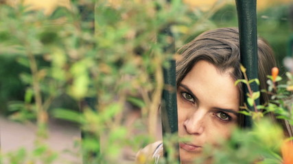 Portrait of sad, unhappy woman looking through fence in garden