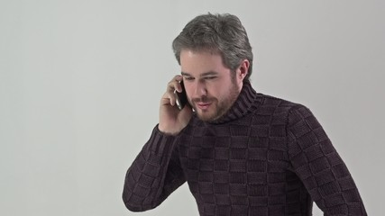 Man in sweater speaks on a mobile phone