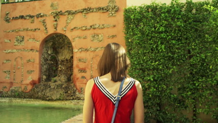 Young woman walking and admiring pool in Alcazar garden