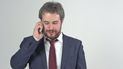 Businessman in suit talking on the phone in studio full video