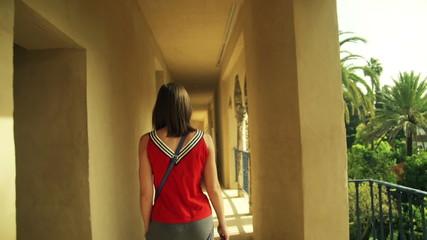 Woman walking through Alcazar terrace in Seville, Spain