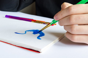 Left hand draws brush with blue paint on paper in album with sev