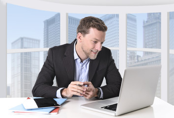 attractive businessman happy at work with office computer