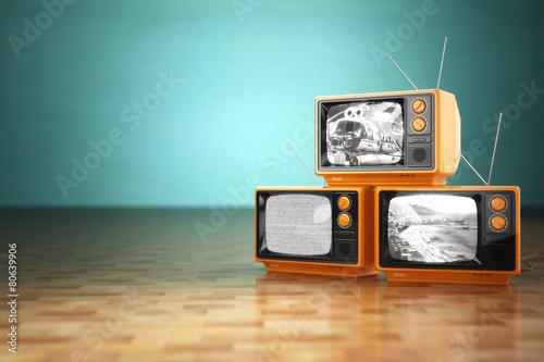 Leinwandbild Motiv Vintage television concept. Stack of retro tv set on green backg