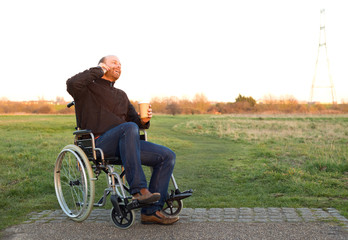 a young man in a wheelchair talking on the phone with a coffee
