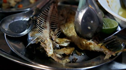 Close-up view on eating grilled mackerel