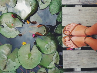 Feet on a edge of lotus pond