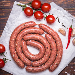 Raw lamb sausage with ingredients for salsa