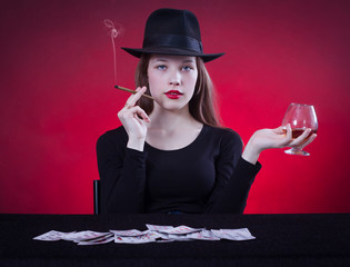 woman playing cards sitting at the table and smoking a cigar.