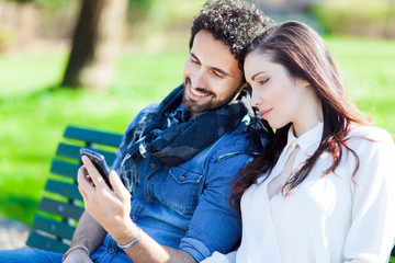 Younf couple on a bench using a smartphone