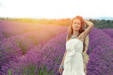 Girl on the lavender field in the rays of the setting sun